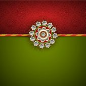 Beautiful white pearl decorated Rakhi on maroon and green background for Raksha Bandhan festival celebrations.