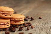 Three coffee macarons on a table with coffee beans