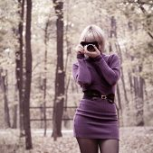 Attractive girl in short dress taking photos in autumn park