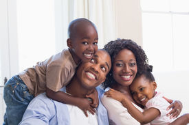 picture of couch  - Happy family posing on the couch together at home in the living room - JPG