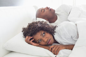 picture of annoying  - Annoyed woman lying in bed with snoring boyfriend at home in the bedroom - JPG
