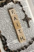 stock photo of rosary  - The word faith displayed on a Bible with a rosary next to a story about having faith - JPG