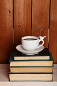 Pile of books with cup on tabletop and wooden background