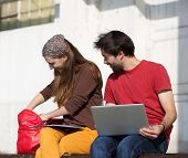 Two Happy Students Sitting Outdoors With Lap Top Computer