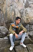 young man in jeans with scarf sitting on a rock at the sea watching the ocean