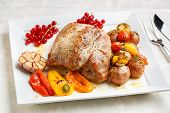 Tasty roasted loin pork with potatoes, bell peppers and gooseberries