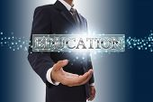Businessman hand showing education button.