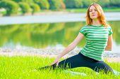 Sportswomen Do Exercises On The Lush Grass In The Park