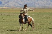 Mongolian woman rides on horseback circa Harhorin, Mongolia.