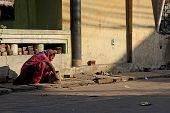 poor Indian Woman Sit On A Ruined Street
