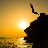Постер, плакат: Boy jumping to the sea Silhouette shot against the sunset sky Boy jumping off a cliff into the oce