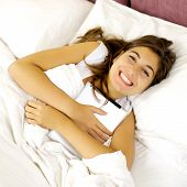 Happy Cute Woman Smiling In Bed Hugging Tablet
