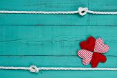 Blank blue wooden sign with collage of red hearts and rope with knots border