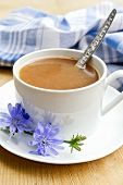 Chicory drink in white cup with spoon and flower on board