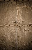 picture of entryway  - aged dark vintage wooden door as background with cuttings and scratch and gold reflex  - JPG