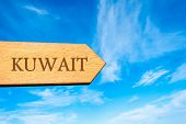 Wooden arrow sign pointing destination KUWAIT poster