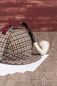 pic of private investigator  - Deerstalker or Sherlock Hat and Tobacco pipe on Old Wooden table - JPG