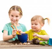 pic of little sister  - Two little sisters are engaged in gardening - JPG