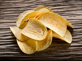 stock photo of potato chips  - Potato chips on a wooden background - JPG
