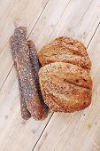 image of baguette  - delicacy french rye breads and baguettes topped with sunflower and poppy seeds over wooden table - JPG