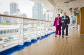 stock photo of passenger ship  - Happy Senior Couple Walking The Deck of a Luxury Passenger Cruise Ship - JPG
