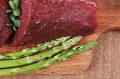 picture of veal  - red fresh raw beef veal fillet with asparagus on cutting plate over wooden table prepared to use - JPG