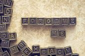 stock photo of forgiveness  - forgive me phrase made from metallic blocks over grunge paper background - JPG