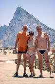 picture of gibraltar  - Portrait of two senior men and middle aged woman posing for photo on the beach with Gibraltar rock on the background - JPG
