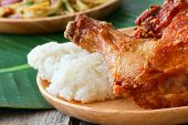 stock photo of thighs  - Deep fried Chicken thigh with sticky rice on wooden plate - JPG