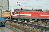 stock photo of locomotive  - locomotive near the crossing with him standing on the machine - JPG