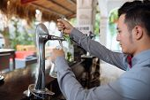 image of bartender  - Bartender pouring fresh draft beer from a tap - JPG