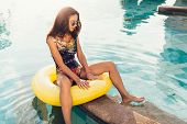 stock photo of mattress  - Young pretty woman with perfect tanned body lying on yellow air mattress in the pool in summer and having fun - JPG
