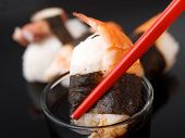 image of soy sauce  - Putting Sushi in a bowl of soy sauce with red chopsticks  - JPG