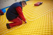 foto of convection  - group of workers installing underfloor heating and colling in modern home - JPG