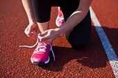 Постер, плакат: Girl ties laces on her sports shoes on running track Horizontal photo