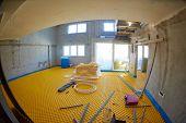 picture of floor heating  - yellow underfloor heating posed in a under construction building - JPG