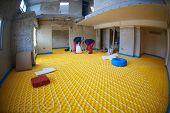picture of floor heating  - group of workers installing underfloor heating and colling in modern home - JPG