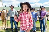 stock photo of horse girl  - cowboy girl with ok gesture closeup portrait on background of her family with horses - JPG
