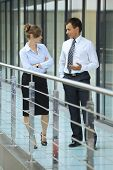 picture of conversation  - Businessman conversing with businesswoman at corridor - JPG