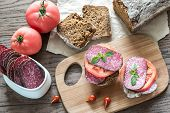 stock photo of tomato sandwich  - Sandwiches With Salami And Tomatoes On The Wooden Board - JPG