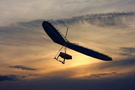pic of glider  - hang glider flying in the sky at sunset - JPG