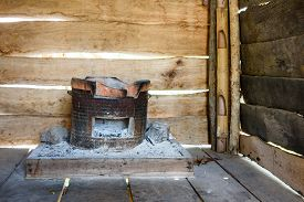 foto of smut  - Traditional charcoal burning clay stove in a rustic wooden house - JPG