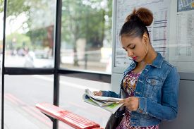 stock photo of bus-shelter  - young woman reading a paper at the bus stop - JPG