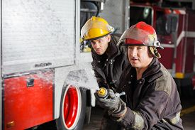 picture of firemen  - Confident young and mature firemen spraying water during training at fire station - JPG