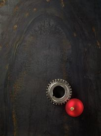 picture of stelles  - Gear and red Christmas ball on the stell plate - JPG