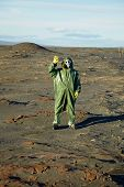 stock photo of scoria  - Strange scientist in overalls and gas masks in the desert - JPG