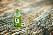 stock photo of scoria  - Green glass bottle from a poison on the ground - JPG