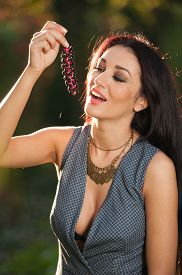 picture of grape  - Beautiful woman in gray posing in autumnal park holding a ripe grapes bunch - JPG