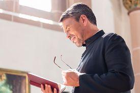 image of priest  - Catholic priest reading bible in church - JPG