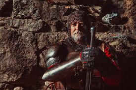 picture of sword  - Old medieval King in armor with sword on the rocks background - JPG